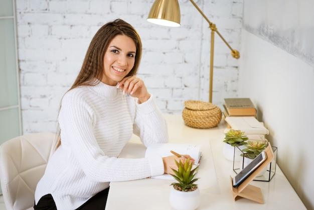 흰색 스웨터에 비즈니스 우먼 테이블에 앉아있는 동안 노트북에 씁니다.