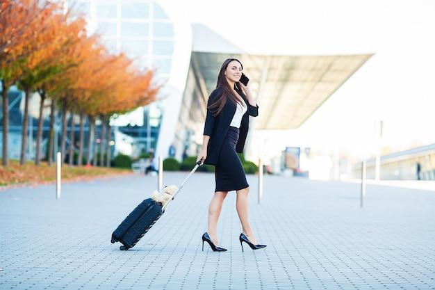 공항 게이트로가는 공항에서 수하물과 함께 걷는 동안 스마트 폰 이야기 공항에서 비즈니스 여자.
