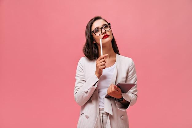 Деловая женщина в бежевом костюме, задумчиво позирует на розовом фоне. задумчивая девушка в светлом стильном наряде держит таблетку на изолированном фоне.