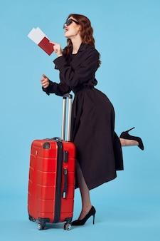 サングラスのプロのエレガントなスタイルの青い背景を身に着けている黒いコートのビジネス女性