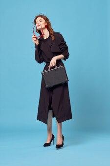 Деловая женщина в черном пальто, носить солнцезащитные очки в профессиональном элегантном стиле на синем фоне