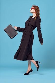 サングラスを身に着けている黒いコートのビジネス女性は青い背景を歩きます。高品質の写真