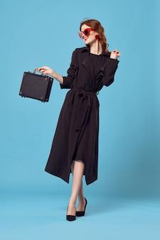 Деловая женщина в черном пальто в темных очках гуляет на синем фоне