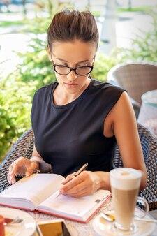 Деловая женщина в черном платье пишет в блокноте