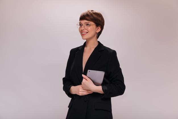黒のスーツを着たビジネスウーマンは、コンピューターのタブレットを保持しています。暗いジャケットを着た短い髪の従業員は、孤立した背景に広く笑顔