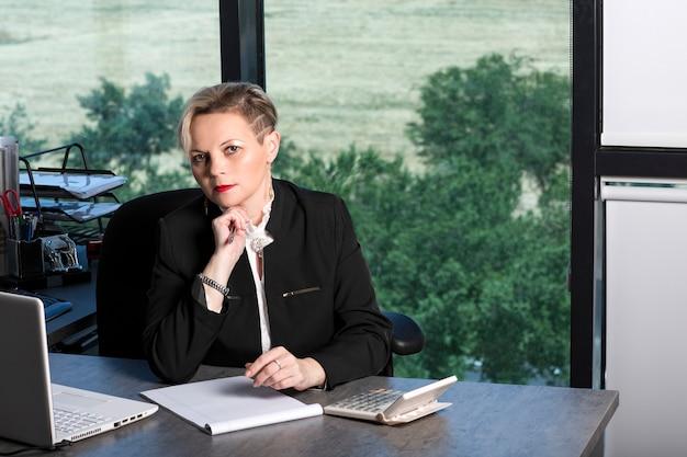 검은 양복을 입은 비즈니스 여성은 노트북 컴퓨터, 계산기를 들고 작업장에 앉아 수심에 찬 표정으로 뺨에 연필을 들고 노트북에 쓰는 작업 일정을 계획합니다.