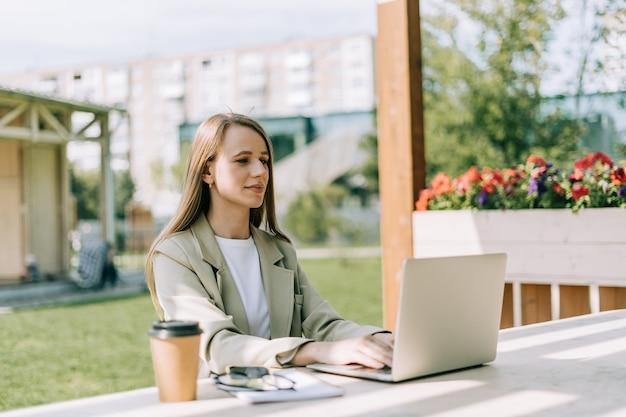 Деловая женщина в пиджаке, работающая на ноутбуке за пределами