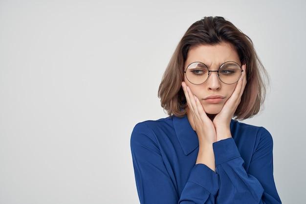 明るい背景をポーズする青いシャツの感情のビジネス女性 Premium写真
