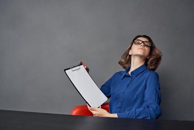 青いシャツを着たビジネスウーマンは、手のドキュメントのテーブルフォルダーに座っています