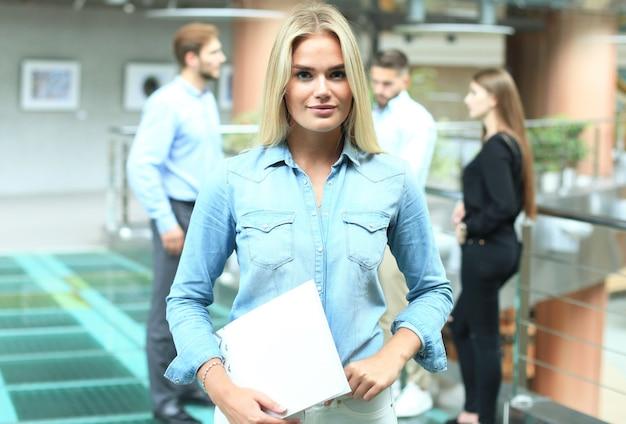 직원들과 평상복을 입은 비즈니스 여성, 현대적인 밝은 사무실의 배경에 있는 사람들.