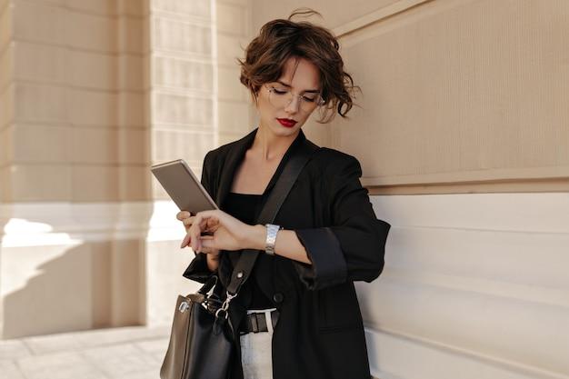 ハンドバッグとタブレットと暗いジャケットを着たビジネスウーマンが通りで時計を見ています。明るい唇のメガネをかけた巻き毛の女性が外でポーズをとる。