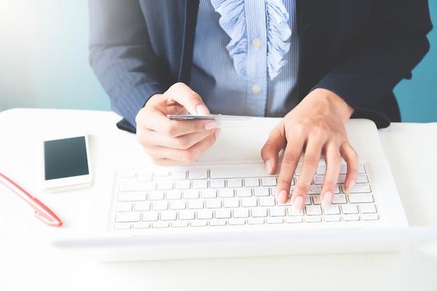검은 양복에 신용 카드를 들고 노트북, 비즈니스 및 온라인 쇼핑 개념을 사용하여 비즈니스 우먼