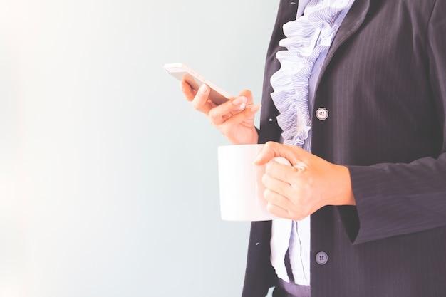 携帯電話とコーヒーのカップ、コピースペースとビジネスコンセプトを保持しているダークスーツのビジネスウーマン
