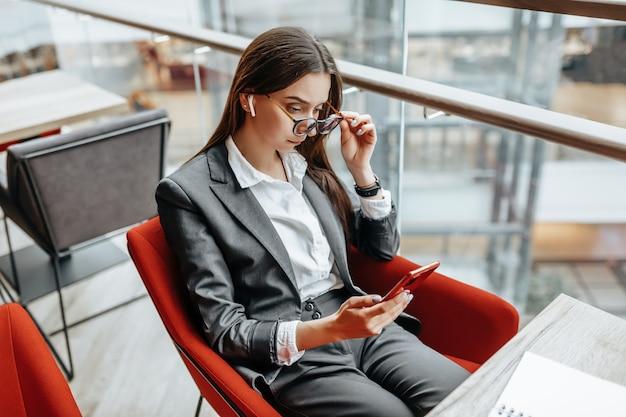 職場で眼鏡をかけているビジネスウーマンは、電話を使用してテーブルに座っています。オフィスのマネージャー。