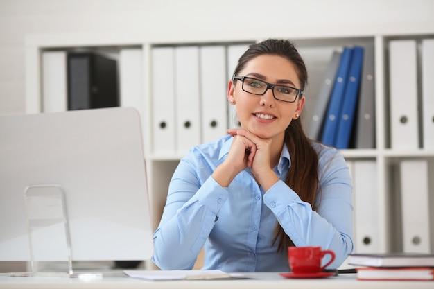 Деловая женщина в очках сидит в кабинете за столом руки держат под подбородком и улыбаются