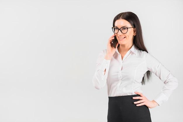 電話で話しているメガネのビジネスウーマン