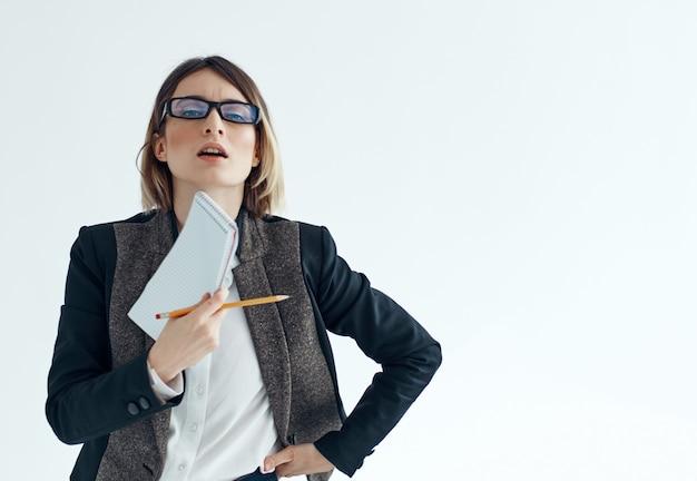 メモ帳ドキュメントオフィスマネージャーと眼鏡をかけたビジネスウーマン。高品質の写真