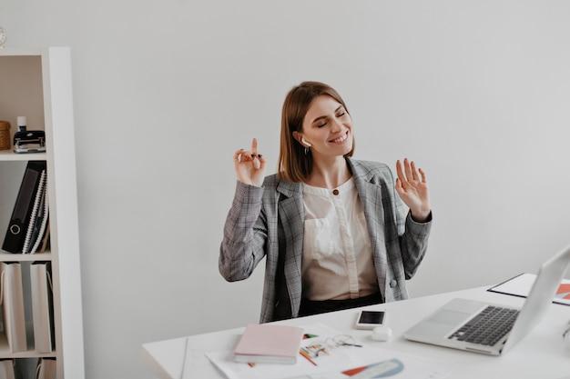 흰색 사무실에서 직장에 앉아있는 동안 음악을 즐기는 회색 재킷에 비즈니스 여자.