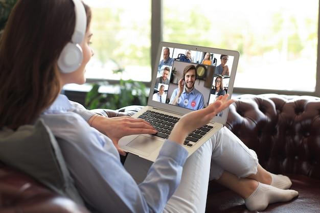 Деловая женщина в наушниках, лежа на диване, разговаривает по видеосвязи с коллегами на онлайн-брифинге во время самоизоляции и карантина. групповая конференция по веб-камере с коллегами на ноутбуке в офисе.