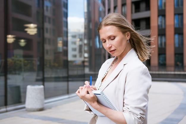 가벼운 재킷을 입은 비즈니스 우먼은 비즈니스 센터 근처에 서서 무언가를 씁니다. 백인 소녀는 공책 목표 계획 업무와 일에 대한 소원 목록에 펜으로 씁니다. 성공한 여성의 메모