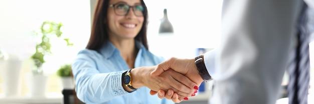 Деловая женщина в офисе пожимает руку деловому партнеру.