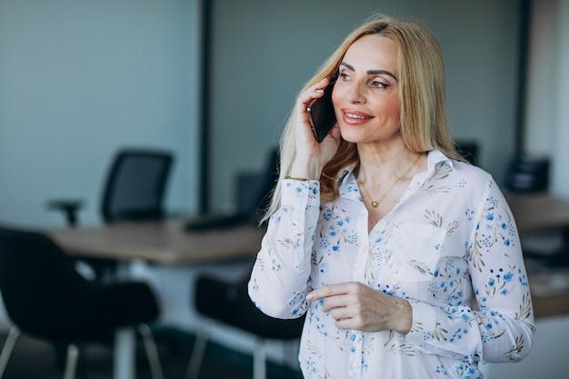 Деловая женщина в офисе с помощью телефона