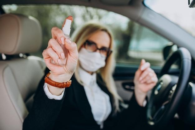 防腐剤を使用して車の中に座っている防護マスクのビジネスウーマン