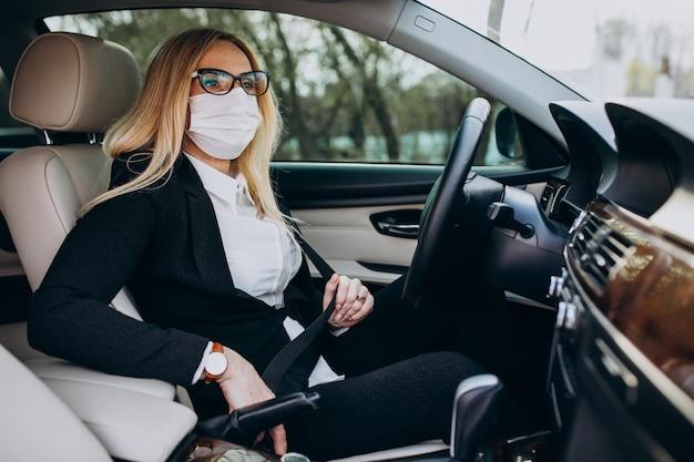 車の中に座っている防護マスクのビジネスウーマン