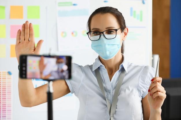 防護マスクのビジネスウーマンはスマートフォンのカメラの肖像画にハローと言う