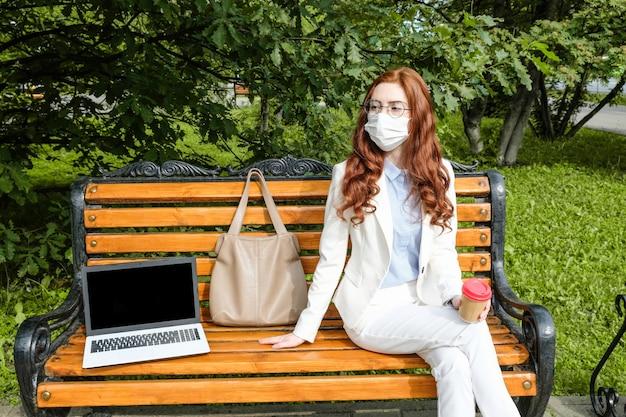 通りに座っている保護マスクのビジネス女性