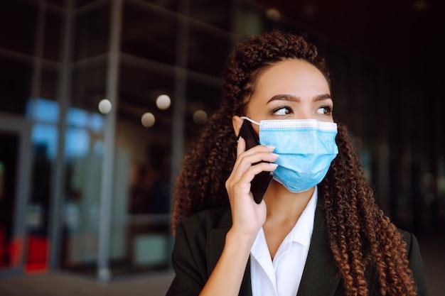 사무실 근처에 서서 전화를 사용하는 보호 의료 마스크를 쓴 비즈니스 여성. 코로나 19.