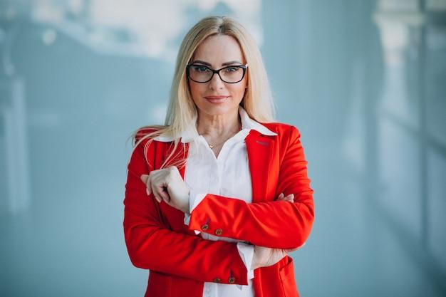 Деловая женщина в красной куртке, изолированных в офисе