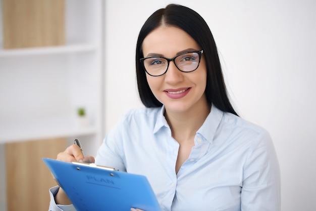 ラップトップコンピューターを使用して、オフィスの机に座ってシャツを着たビジネス女性。