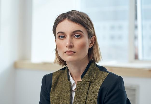 Деловая женщина в костюме возле окна в портретной куртке обрезанный вид