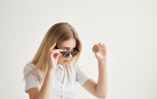 サングラスをかけたビジネスウーマンは、インターネットファイナンスでビットコインゴールドの暗号通貨を保有しています。