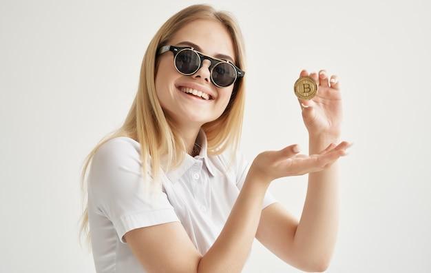 サングラスのビジネスウーマンは、インターネット金融の手でビットコインゴールド暗号通貨を保持しています