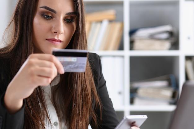 オフィスでのビジネスの女性は彼女の手でプラスチック製のクレジットデビットカードを保持しています。