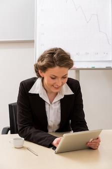 직장에서 태블릿 점원을 찾고 사무실에서 비즈니스 우먼