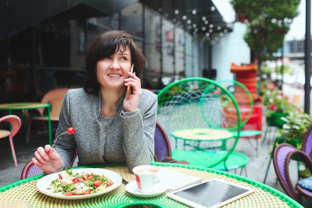 電話で話していると、サラダを食べてカフェのテラスでのビジネスの女性