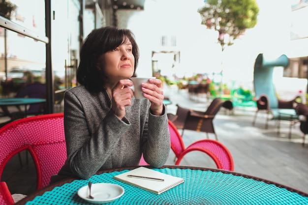カフェのテラスでのビジネスの女性