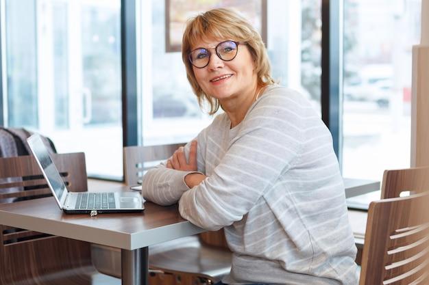 オフィスの窓で職場のビジネスウーマン。中年の女性がカフェのノートパソコンで働いています。彼女は眼鏡をかけています