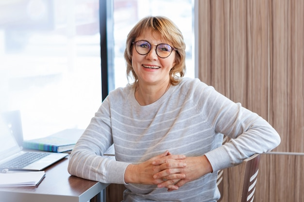 オフィスの職場でのビジネスウーマン。中年の女性がカフェのノートパソコンで働いています。彼女は眼鏡をかけて笑っています。