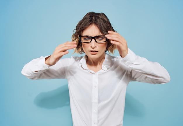 白いシャツとメガネワーキングオフィス青い背景のビジネス女性