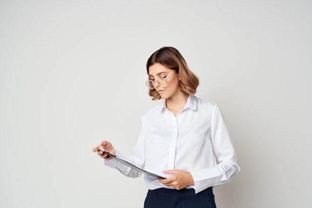 白いシャツを着たビジネスウーマンは、オフィスマネージャーを文書化します