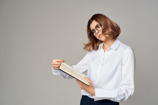 白いシャツのドキュメントのビジネスウーマンは公式に働きます