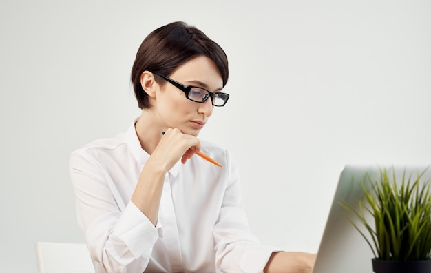 Деловая женщина в белой рубашке сидит за рабочим столом, помощник специалистов по офисным технологиям
