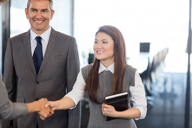 Business woman interacting and shaking hands with team in office