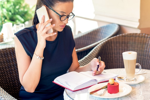 ビジネスの女性がカフェを呼んでいます。