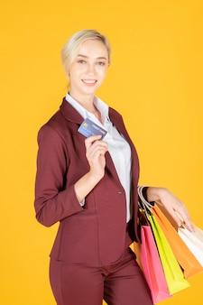 ビジネスの女性はスタジオの黄色の背景で買い物に満足しています。