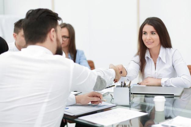 비즈니스 우먼이 직장 회의에서 직원과 악수하고 있습니다.팀워크
